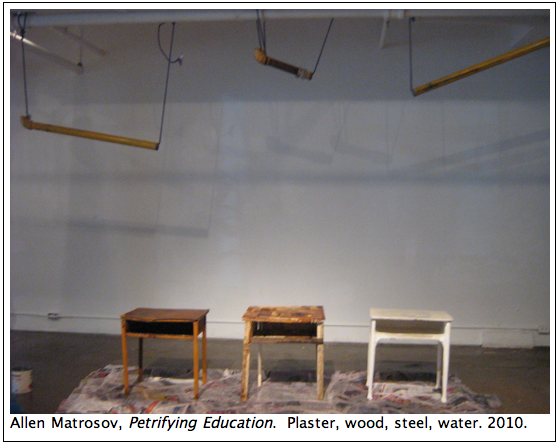 "Allen Matrosov's ""Petrifying Education"" critiques education by allowing desk materials to break apart under the indifferent force of dripping pipe water."