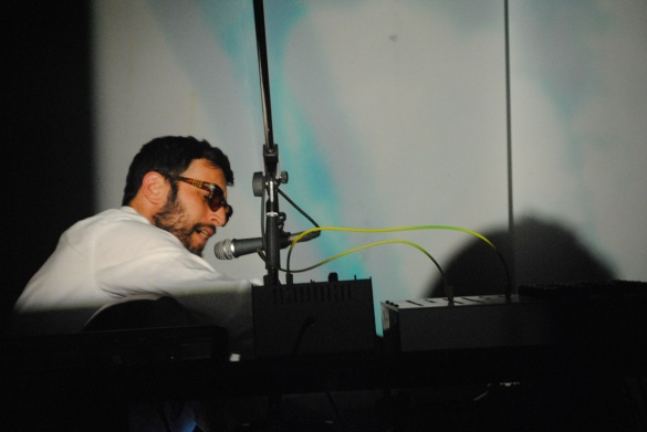 Radwan Ghazi Moumneh sings while tweaking delay speeds as Malena Szlam Salazar uses three 16mm projectors to send visuals onto screens behind him on the stage. Photo: Tom Beedham